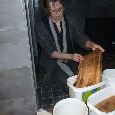 Katri Kokko parkitsee kalannahkoja kotonaan pesuhuoneessa.