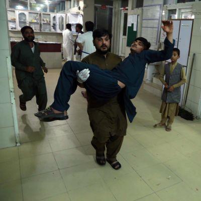 Mies kantaa haavoittunutta sairaalan käytävällä