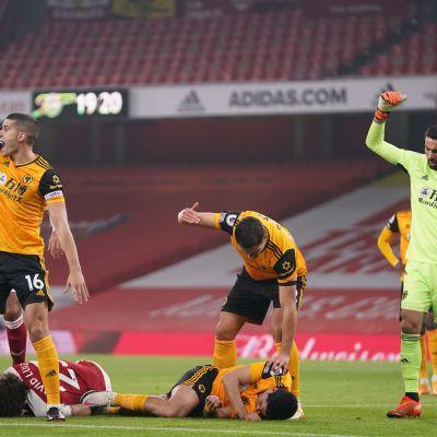 Raul Jimenez makaa maassa, muut pelaajat viittovat apua kentälle.