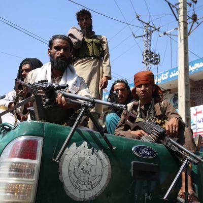 Tuiman näköisiä talibantaistelijoita avolava-auton kyydissä.