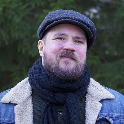 En man med skägg och basker på huvudet och halsduk runt halsen ler lite.