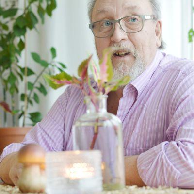 Peter sitter vid matbordet med en kopp kaffe i handen.