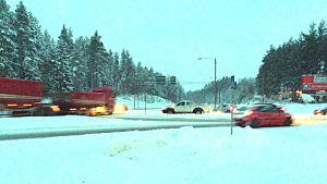 En landsvägskorsning och snöigt landskap. Långtradare och bilar kör i olika riktningar. Vägen ser hal ut. Det är skymning.