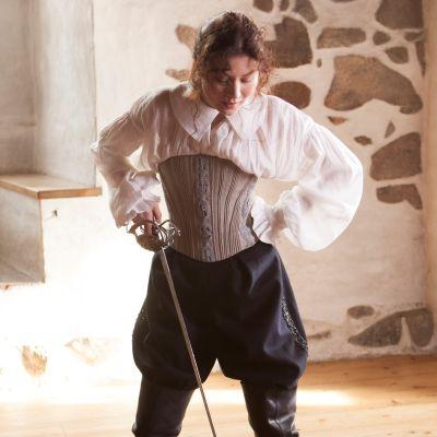 Nuori nainen katsoo alaspäin miekka kädessään. 1600-luku, kuningatar Kristiina.