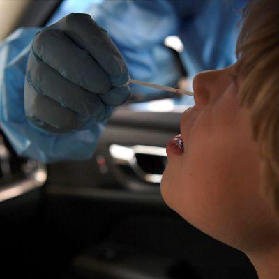 Barn coronatestas i bilen.