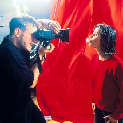 Irène Jacob poseeraa valokuvaajalle elokuvassa Kolme väriä: Punainen