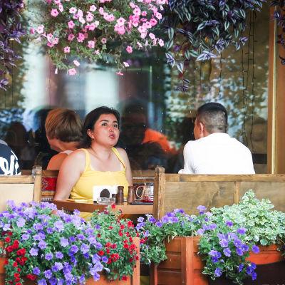 Människor sitter på en uteservering och talar och äter.