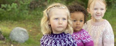 Tre flickor iklädda handstickade strömsötröjor i barnstorlekar
