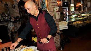 Man med rött förkläde serverar tryffelpasta på restaurang i staden Fabriano.