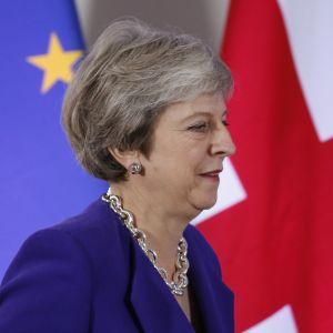 Theresa May i profil, i bakgrunden EU:s och Storbritanniens flaggor.