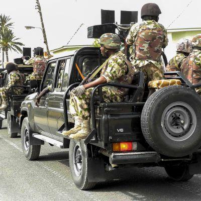 Sotilaita sotilasajoneuvojen kyydissä.