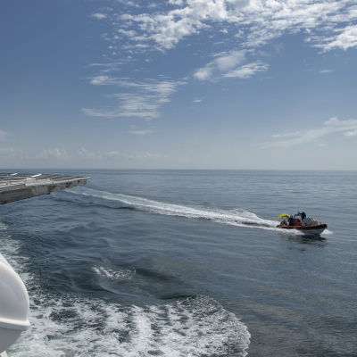 Bild på hav, på bilden syns ett större fartyg där bilden är tagen i från och en mindre snabb båt.