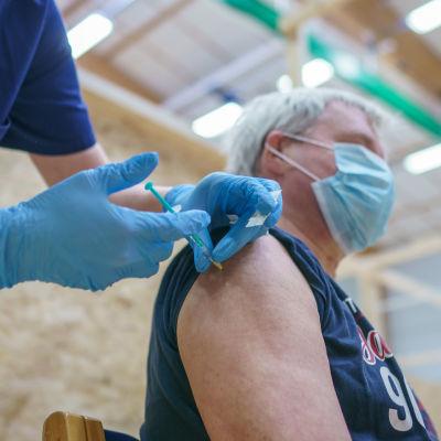 En man blir stucken med en spruta innehållande coronavaccin, av en sköterska i mörkblå kläder och ljusblå gummihandskar.