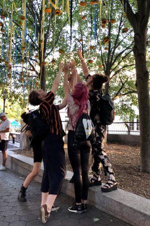 Besökare försöker nå solrosorna som är upphängda i träden vid ingången till midsommarfesten i New York.