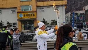 Man klädd i vita kläder bär en brinnande facka. Några andra människor synd framför och bakom honom.