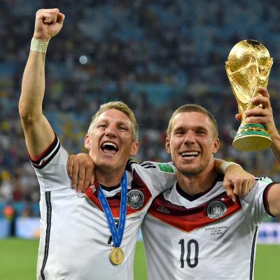 Bastian Schweisteiger och Lukas Podolski firar VM-guldet i fotboll.