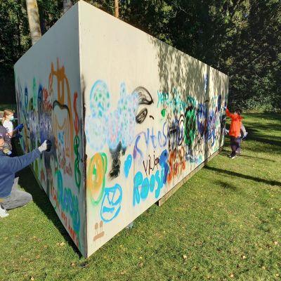 En triangelformad vägg eller ett plank som placerats ute på en gräsmatta. Barn och ungdomar målar på det.