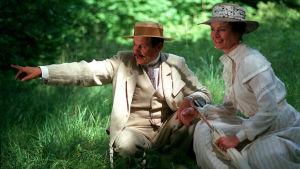 Nainen ja mies kyykyssä maassa. Mies osoittaa kuvan vasempaan laitaan. Vaatteet 1900-luvun alusta.