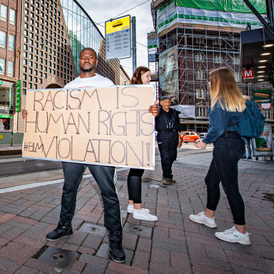 """Arnold Siku pitelee kylttiä jossa lukee """"Racism is human rights violation""""."""