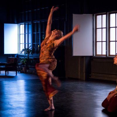 Naistanssija tanssii kädet ilmassa näyttämöllä. Miestanssija istuu vieressä.