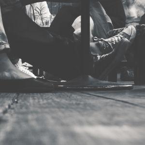 Personer sitter på en bänk, endast fötterna syns.