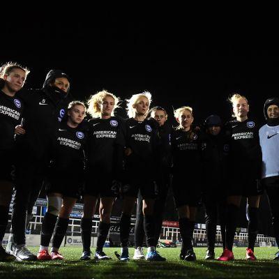 Brighton Hove & Albionin pelaajat nojaavat toisiinsa ringissä.