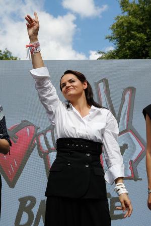Svetlana Tichanovskaja står med handen uppsträckt och hälsar på sina anhängare vid ett valmöte i staden Baranovichi.