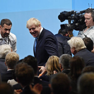 Boris Johnson omringad av kameror.