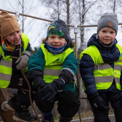 Kolme poikaa istuu kiipeilytelineessä esikoulun pihalla.