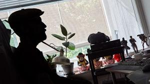 En man med keps i skägg i svart siluett sitter vid en dator med ljusa gardiner fördragna. På fönsterbrädet sitter leksaksapor med randiga byxor.