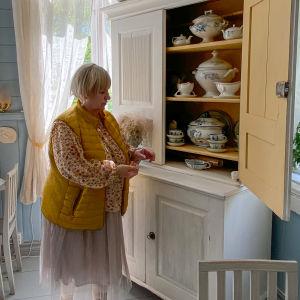 En kvinna står invid ett öppet skåp med antikt porslin.