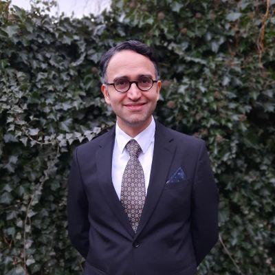 Man i kostym står mot en buske och ler mot kameran.