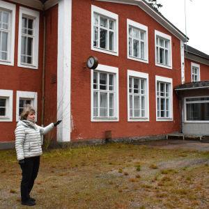 Mayvor Ekholm i vinterkläder framför den tegelröda byggnaden Björkboda skola.