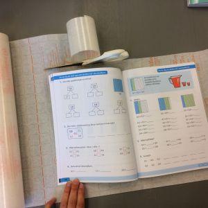 Uppslagen bok som ligger på bokplast med skyddspapper
