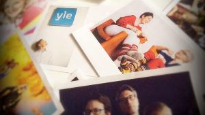 Sekalaisia kuvia pöydällä, yhdessä kuvassa Ylen logo