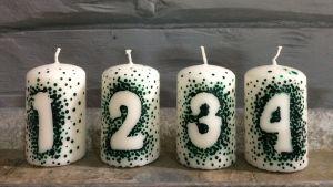 Fyra vita ljus med siffrorna 1-4 formade av gröna prickar