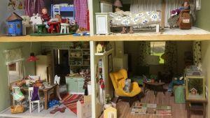Ett inrett dockhus i två våningar med fyra rum fyllda med handgjorda miniatyrer.
