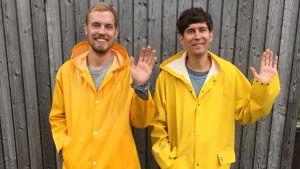 Kasper och Jussi Virta vinkar i gula regnrockar