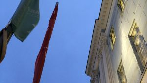 Två ihopvirade flaggor och en jugendfasad pekar upp mot skyn i blå timmen.