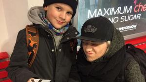 Äiti ja poika metrossa. Poika hymyilee kameralle ja äiti ilveilee.