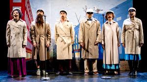 Joukko ylioppilaita laulaa rivissä, lakit päässään, beige trenssi yllään. Mukana näyttelijät  Sara Melleri, Juho Milonoff, Jarkko Lahti, Paavo Kinnunen, Vilma Melasniemi ja Eeva Soivio.