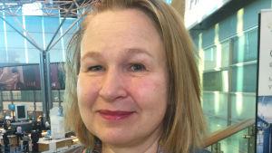 Medelålders kvinna på flygfält tittar in i kameran