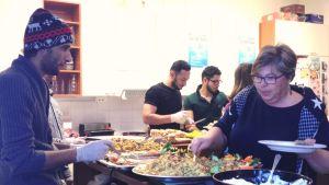 En kvinna tar mat från brickor och skålar. Män står bakom disken.