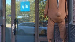 """Ylen nallepuku ilman päätä """"selin"""" tuulettumassa puvuston porstuan ulkopuolella, Ylen logo näkyy, kesä/syysaikaa, päivä"""