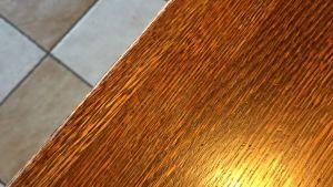 Ravintolapöytää ja lattiaa, valon kajoa oikeassa alakulmassa