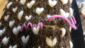 Tummärkning med rosa garn på stickad vante