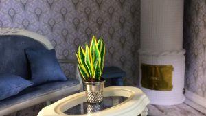 Nukkekodin olohuone missä viherkasvi sohvapöydällä.