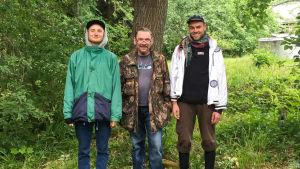 Juha Kumara, Matti Kemi ja Helge seisovat vehreyden keskellä ja hymyilevät kameralle.