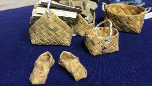Miniatyrmodellleer av näverhantverk föreställande tofflor, vedkorg och flätade korgar.