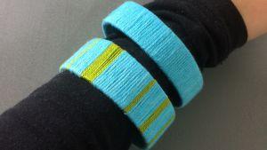 Arm med två armband gjorda av garn.